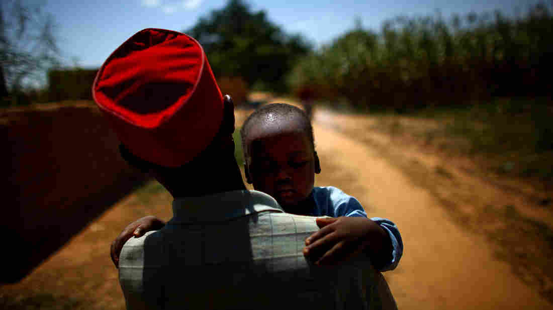 Ado Ibrahim carries his son Aminu through a village in northern Nigeria. Aminu was paralyzed by polio.
